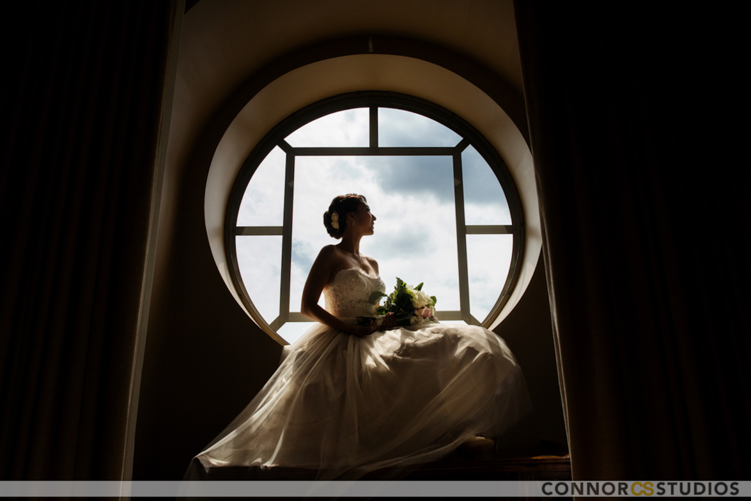 beautiful bride in strapless gown posing in window
