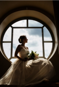 bride sitting for pictures in a window well